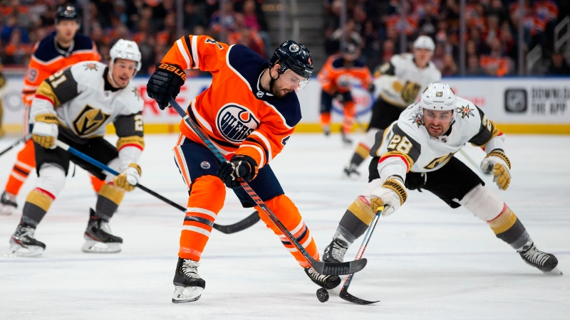 Edmonton Oilers Kris Russell (4) is checked by Vegas Golden Knights' William Carrier (28) during first period NHL action in Edmonton on Monday, March 9, 2020. THE CANADIAN PRESS/Codie McLachlan