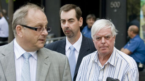Escorted by police, financial adviser Earl Jones, right, accompanied by his lawyer Jeffrey Boro, left, leaves an office tower in Montreal, Monday, July 27, 2009. (THE CANADIAN PRESS/Graham Hughes)