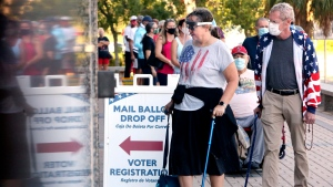 In this Monday, Oct. 19, 2020, file photo, voters Jenny Hart, center, and James Hart, of Clearwater, wait in line to enter the Supervisor of Elections Office at the Pinellas County Courthouse during early voting in Clearwater, Fla. Florida's Pinellas County is one to watch on election night. It was one of only four counties in Florida to switch from Obama to Trump.  (Douglas R. Clifford/Tampa Bay Times via AP, File)