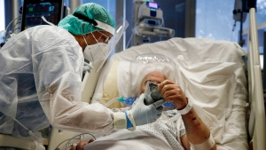 Medics tend to a COVID-19 patient at the intensive care unit of Casal Palocco hospital in Rome Tuesday, Oct. 20, 2020. (Cecilia Fabiano/LaPresse via AP)