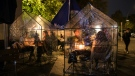 Guests sit in plastic tents as a protection measure against COVID-19 at a coffee shop and bar in Berlin. (AFP)