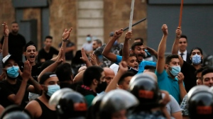 Supporters of former Lebanese Prime Minister Saad Hariri shout slogans against anti-government protesters who denouncing the naming of Hariri as a potential candidate as the country's new prime minister, in downtown Beirut, Lebanon, Wednesday, Oct. 21, 2020. (AP Photo/Hussein Malla)