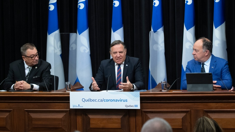 Quebec Premier Francois Legault responds to reporters questions during a news conference on the COVID-19 pandemic, Tuesday, October 20, 2020 at the legislature in Quebec City. Horacio Arruda, Quebec director of National Public Health, left, and Quebec Health Minister Christian Dube, right, look on. THE CANADIAN PRESS/Jacques Boissinot