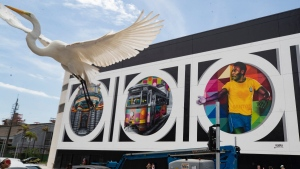 A bird flies and people walk past a mural created by Brazilian street artist Eduardo Kobra to pay homage to soccer legend Pele to mark his 80th birthday in the coastal city of Santos, Brazil, on Oct. 18, 2020. (Andre Penner / AP)