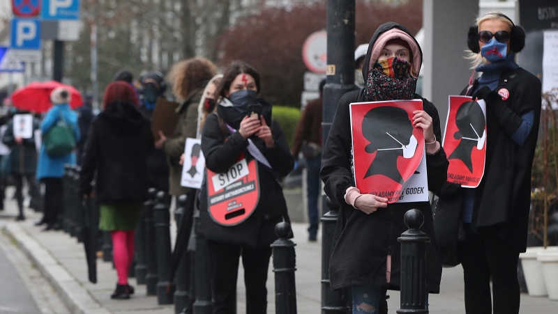 FILE - Women's rights activists, wearing masks against the spread of the coronavirus, protest against a draft law tightening Poland's strict anti-abortion law in Warsaw, Poland, on Wednesday, April 15, 2020. (AP Photo/Czarek Sokolowski)