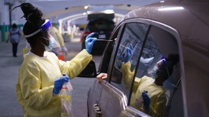 A nurse performs a test on a patient at a drive-in COVID-19 clinic in Montreal, on Wednesday, October 21, 2020. THE CANADIAN PRESS/Paul Chiasson