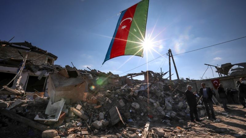 Azerbaijan's national flag flies over destroyed houses in a residential area that was hit by rocket fire overnight by Armenian forces, on Thursday, Oct. 22, 2020 in Ganja, Azerbaijan's second largest city, near the border with Armenia. (AP Photo/Aziz Karimov)