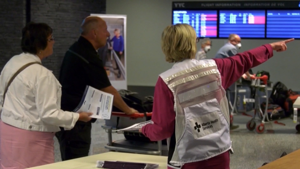 An Alberta Health Services representative directs arriving passengers at the Calgary International Airport during the COVID-19 pandemic (file)