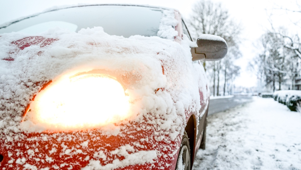 A red Sedan can be seen covered in snow.  (Skitterphoto/ Pexels)