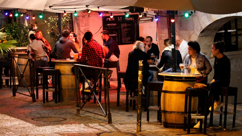 People drink in a bar terrace before the start of a new coronavirus curfew, in Bayonne, southwestern France, Thursday, Oct. 22, 2020. (AP Photo/Bob Edme)