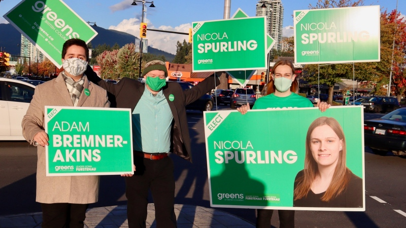 Nicola Spurling (right) waves signs for her political campaign with supporters on Wednesday Oct. 21 (Photo Twitter).