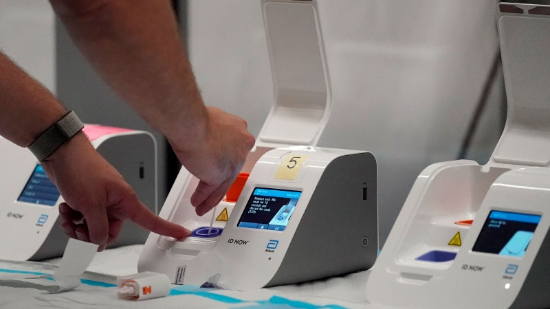 Dignity GoHealth worker Brandon Hastings uses an Abbott ID Now rapid antigen testing machine for United Airlines passengers who took tests at the SFO COVID-19 rapid testing site at San Francisco International Airport in San Francisco, Thursday, Oct. 15, 2020. (AP Photo/Jeff Chiu)