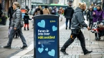 "People walk past a trash can with a sign reading ""The danger is not over - Keep your distance"" in the Swedish city of Uppsala. (AFP)"