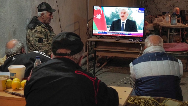 Armenians watch Azerbaijan's President Ilham Aliyev speaking on television as they take refuge in a bomb shelter in Stepanakert, Nagorno-Karabakh, on Oct. 22, 2020. (AP)