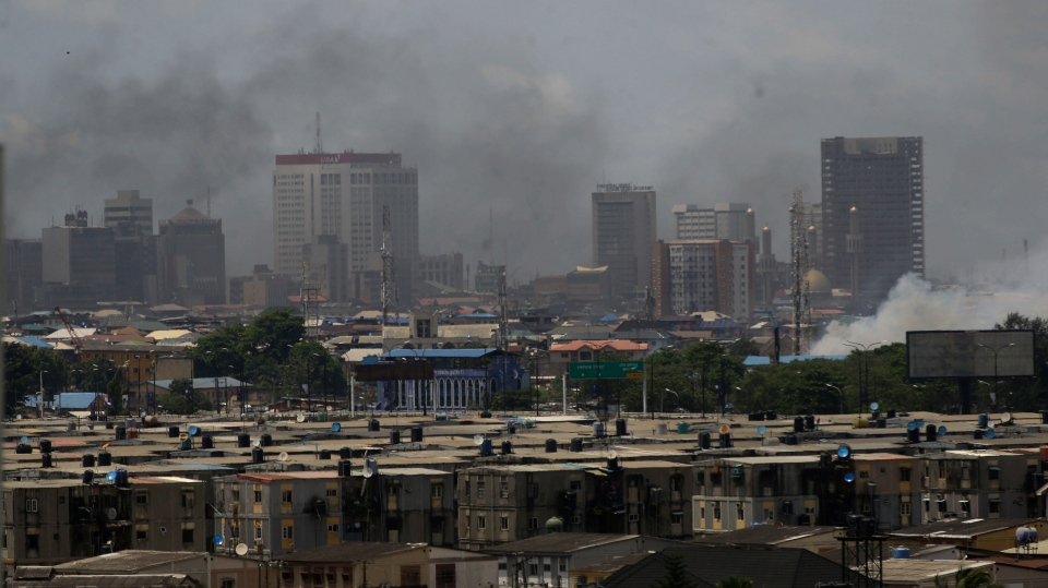 Smokes rise from government buildings set on fire by protesters in Lagos, Nigeria, Wednesday Oct. 21, 2020. Nigerians protesting against police brutality stayed on the streets in Lagos on Wednesday, breaking the government curfew following a night of chaotic violence in which demonstrators were fired upon, sparking global outrage. ( AP Photo/Sunday Alamba)