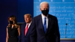 first lady Melania Trump, left, and President Donald Trump, center, remain on stage as Democratic presidential candidate former Vice President Joe Biden, right, walk away at the conclusion of the second and final presidential debate Thursday, Oct. 22, 2020, at Belmont University in Nashville, Tenn. (AP Photo/Julio Cortez)