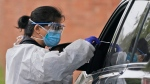 Medical personnel prepare to administer a COVID-19 swab at a drive-through testing site in Lawrence, N.Y., Wednesday, Oct. 21, 2020. (AP Photo/Seth Wenig)