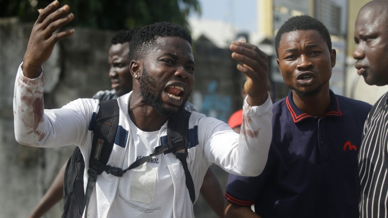 Alister, a protester who says his brother Emeka died from a stray bullet from the Army, reacts while speaking to Associated Press near Lekki toll gate in Lagos, Nigeria, Tuesday Oct. 20, 2020. After 13 days of protests against alleged police brutality, authorities have imposed a 24-hour curfew in Lagos, Nigeria's largest city, as moves are made to stop growing violence. ( AP Photo/Sunday Alamba)