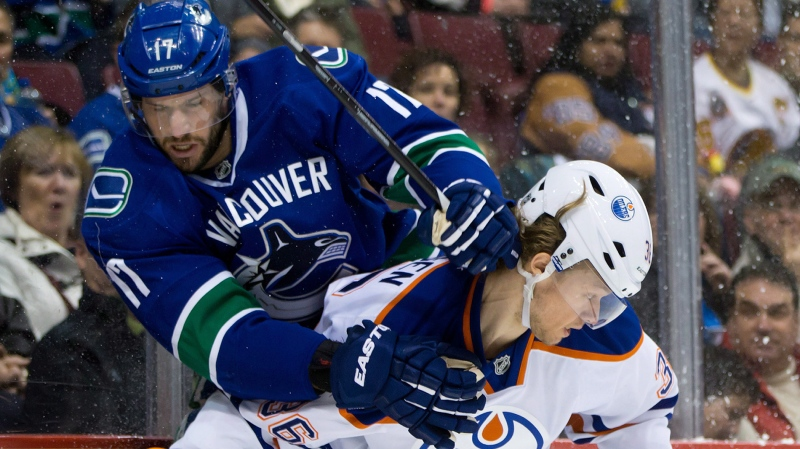 Vancouver Canucks' Ryan Kesler, left, and Edmonton Oilers' Philip Larsen, of Denmark, collide during first period NHL hockey action in Vancouver, B.C., on Friday Dec. 13, 2013. (THE CANADIAN PRESS/Darryl Dyck)