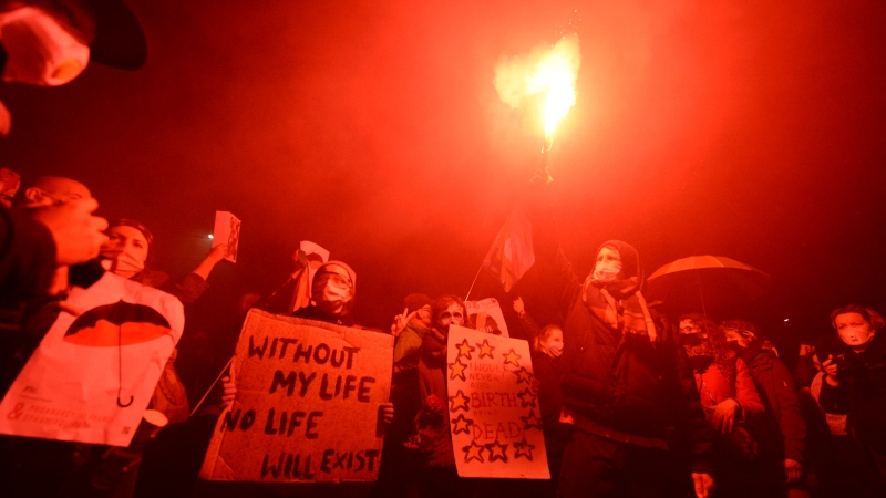 A crowd gathers outside the house of Poland's ruling conservative party leader Jaroslaw Kaczynski in Warsaw, Poland, Friday, Oct. 23, 2020. Protesters vented anger for a second day across Poland over a court ruling that declared abortions of fetuses with congenital defects unconstitutional. (AP Photo/Czarek Sokolowski)