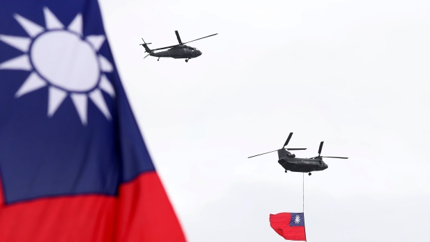 Helicopters fly over President Office with Taiwan National flag during the National Day celebrations in Taipei, Taiwan, Saturday, Oct. 10, 2020. (AP Photo/Chiang Ying-ying)