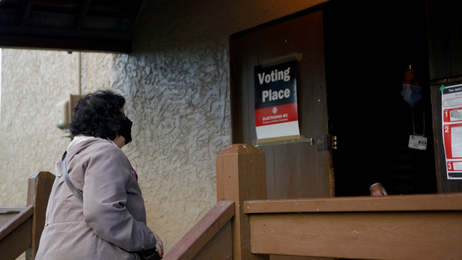A woman arrives to cast her vote during the advance polls for the provincial election in Langford, B.C., Monday, Oct. 19, 2020. THE CANADIAN PRESS/Chad Hipolito