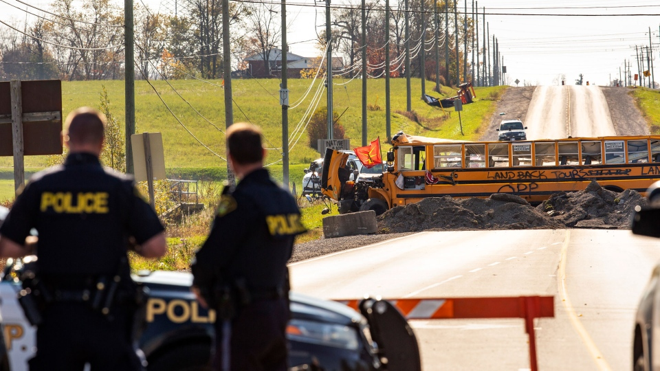 Ontario Provincial Police stand at a blockade on Argyle Street South in Caledonia, Ont., after a judge granted a permanent injunction against a land reclamation camp known as 1492 Land Back Lane Friday, October 23, 2020. THE CANADIAN PRESS/Tara Walton