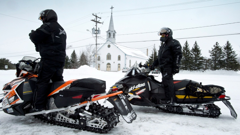American tourists stop in front of the parish church Friday, March 1, 2013, as a major snowmobile trail passes through La Motte, Que. The Quebec town braces for possible life as an international pilgrimage site should Marc Cardinal Ouellet be elected pope this week. THE CANADIAN PRESS/Paul Chiasson
