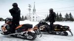 American tourists stop in front of the parish church Friday, March 1, 2013, as a major snowmobile trail passes through La Motte, Que. THE CANADIAN PRESS/Paul Chiasson