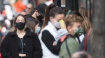 People wear face masks as they wait to enter a store in Montreal, Sunday, Oct. 18, 2020, as the COVID-19 pandemic continues in Canada and around the world. THE CANADIAN PRESS/Graham Hughes