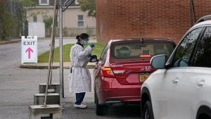 In this Oct. 21, 2020, file photo, medical personnel prepare to administer a COVID-19 swab at a drive-through testing site in Lawrence, N.Y. (AP Photo/Seth Wenig, File)