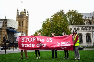 Demonstrators wearing pig masks hold a banner against the tread deal between the UK and the US, in Parliament Square, as part of a day of action against the US trade deal, ten days before the US Presidential election, in London, Saturday, Oct. 24, 2020. There will will be protests held nationwide against a proposed US trade deal, opposed by a number of organisations including Global Justice Now and Stop Trump Coalition. (AP Photo/Alberto Pezzali)