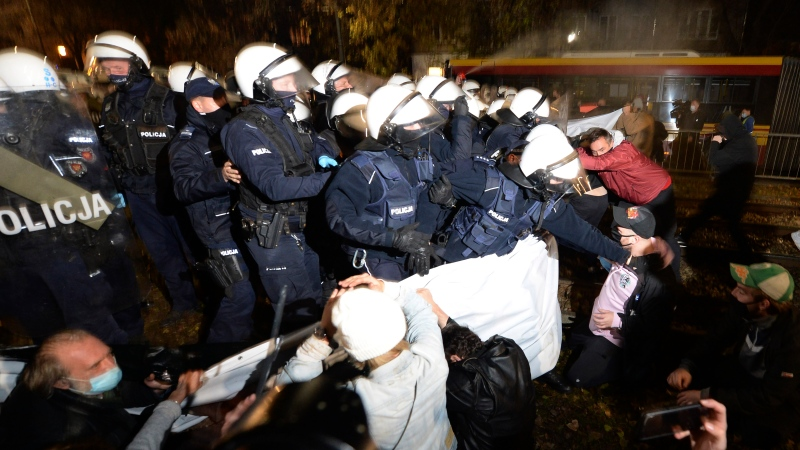 Police confront with protesters who gathered before the house of Poland's ruling conservative party leader Jaroslaw Kaczynski to protests a decision by the Constitutional Court, in Warsaw, Poland, on Friday, Oct.23, 2020. Poland's top court ruled Thursday that a law allowing abortion of fetuses with congenital defects is unconstitutional, shutting a major loophole in the predominantly Catholic country's abortion laws that are among the strictest in Europe. Defying the pandemic-related ban on gatherings, the protesters chanted for the government to resign. (AP Photo/Czarek Sokolowski)