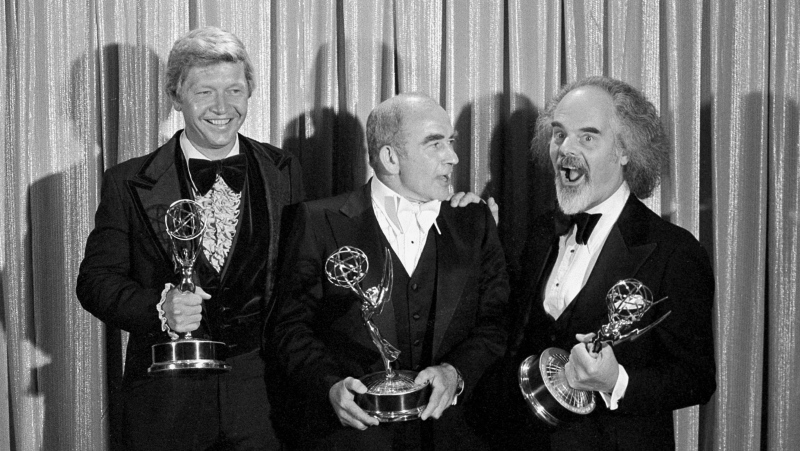 "FILE - In this Sunday, Sept. 11, 1977 file photo, Screenwriter William Blinn, left, Ed Asner, center, and David Greene pose with their Emmy statuettes at the annual Primetime Emmy Awards presentation in Los Angeles. William Blinn, a screenwriter for the landmark TV projects ""Brian's Song"", ""Roots"" and the Prince film ""Purple Rain,"" has died, Thursday, Oct. 22, 2020. He was 83. (AP Photo/File)"