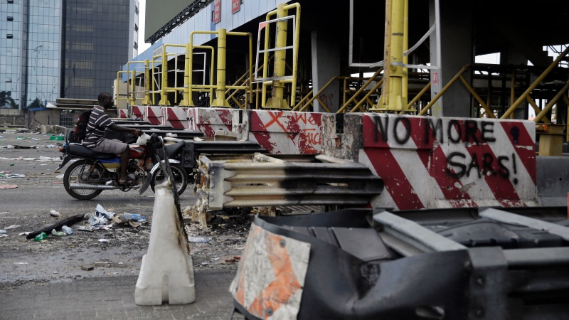 People drive past burnt toll gates with anti police slogans sprayed across, in Lagos Friday, Oct. 23, 2020. (AP Photo/Sunday Alamba)