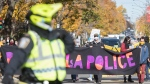 People take part in a defund the police protest in Montreal, Saturday, October 24, 2020, as the COVID-19 pandemic continues in Canada and around the world. THE CANADIAN PRESS/Graham Hughes