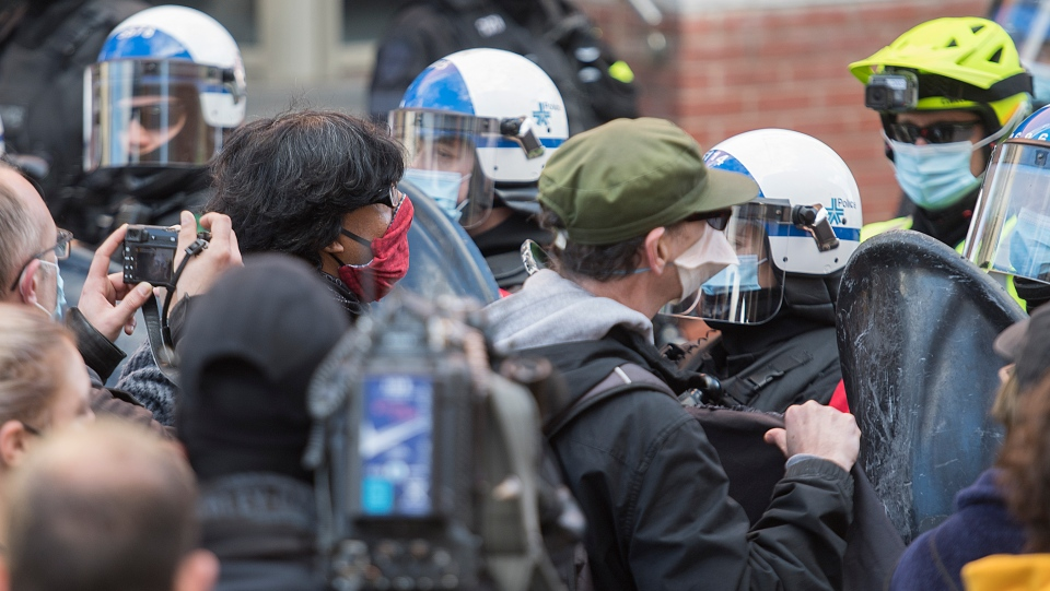 Protesters confront police during a defund the police demonstration in Montreal, Saturday, October 24, 2020, as the COVID-19 pandemic continues in Canada and around the world. THE CANADIAN PRESS/Graham Hughes