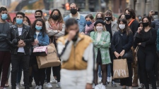 People wear face masks as they watch a street performer in Montreal, Saturday, October 24, 2020, as the COVID-19 pandemic continues in Canada and around the world. THE CANADIAN PRESS/Graham Hughes