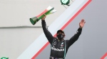 Mercedes driver Lewis Hamilton of Britain holds up the trophy on the podium after his record breaking win during the Formula One Portuguese Grand Prix at the Algarve International Circuit in Portimao, Portugal, Sunday, Oct. 25, 2020. (Jose Sena Goulao, Pool via AP)