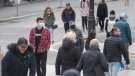 People wear face masks as they walk along a street in Montreal, Sunday, October 25, 2020, as the COVID-19 pandemic continues in Canada and around the world. (THE CANADIAN PRESS/Graham Hughes)
