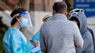 A health-care worker talks with people as they wait to be tested for COVID-19 at a testing clinic in Montreal, Sunday, October 4, 2020, as the COVID-19 pandemic continues in Canada and around the world. THE CANADIAN PRESS/Graham Hughes
