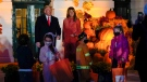 U.S. President Donald Trump and first lady Melania Trump greet trick-or-treaters on the South Lawn during a Halloween celebration at the White House, Sunday, Oct. 25, 2020 in Washington. (AP Photo/Manuel Balce Ceneta)