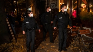 A patrol of the federal police goes along Kollwitz-Platz in Berlin, Germany, Saturday, Oct.24, 2020. In connection with the corona restrictions, numerous police officers checked during the night that the curfew and contact restrictions were being observed. (Paul Zinken/dpa via AP)