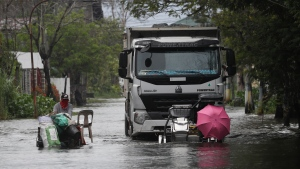 Motorists with an umbrella negotiate a flooded road due to Typhoon Molave in Pampanga province, northern Philippines, Monday, Oct. 26, 2020. (AP Photo/Aaron Favila)
