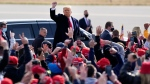 U.S. President Donald Trump acknowledges supporters as he leaves a campaign rally at Manchester-Boston Regional Airport, Sunday, Oct. 25, 2020, in Londonderry, N.H. (AP Photo/Elise Amendola)