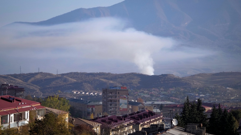 Smoke rises after shelling by Azerbaijan's artillery during a military conflict in Stepanakert, the separatist region of Nagorno-Karabakh, Saturday, Oct. 24, 2020. (AP Photo)