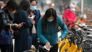 A woman wearing a face mask to help curb the spread of the coronavirus uses an alcohol tissue to disinfect a bicycle of bike-sharing companies during the morning rush hour in Beijing, on Oct. 26, 2020. (Andy Wong / AP)
