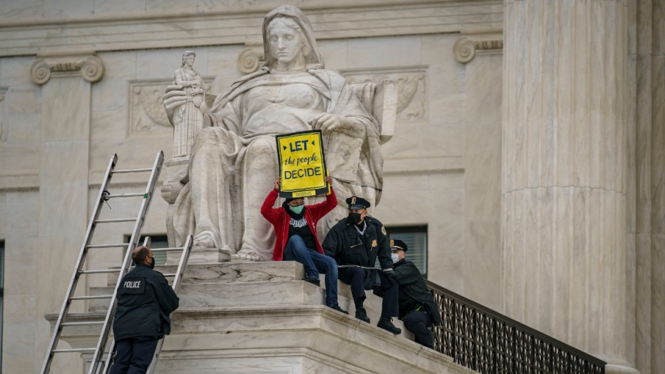 A protester opposed to the Senate's race to confirm Amy Coney Barrett is removed by police after chaining themselves to a railing and holding a sign while sitting atop the statue Contemplation of Justice, at the Supreme Court building in Washington, on Oct. 25, 2020. (J. Scott Applewhite / AP)
