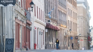 A sandwich board is shown on an almost empty street in Old Montreal, Sunday, October 25, 2020, as the COVID-19 pandemic continues in Canada and around the world. THE CANADIAN PRESS/Graham Hughes