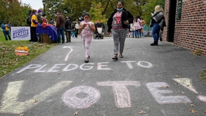 People walk past writing on the sidewalk ahead of a 'Pledge to Vote' event with U.S. Rep. Alexandria Ocasio-Cortez, in the Bronx borough of New York, on Oct. 25, 2020. (Kathy Willens / AP)